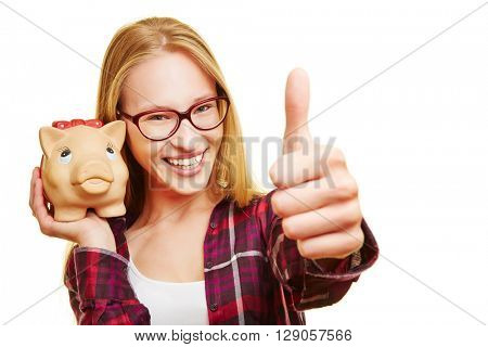 Smiling happy woman with piggy bank holding her thumbs up