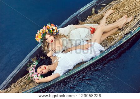 Two young women on boat at sunset. The girls has a colorfull make-up and flower wreath on they head, relaxing and sailing on the river. Beautiful sexy slim body and cute face.  Concept of female beauty, rest on the nature, and wate
