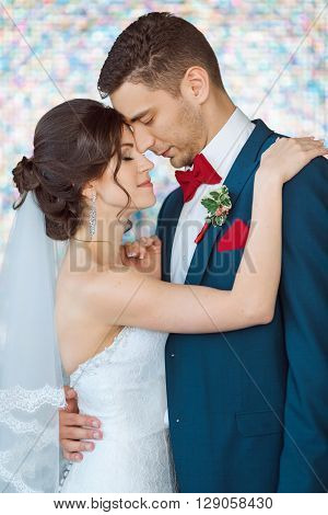 Wedding couple in love. Beautiful bride in white dress and veil with handsome groom in blue suite standing and embracing each other indoors against beautiful colored background bokeh like their dreams. Close-up portrait of man and girl with closed eyes