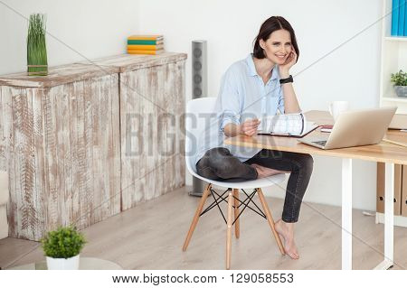 Beautiful young woman is doing paperwork at home. She is sitting on chair at table and touching papers. The lady is looking at camera and smiling