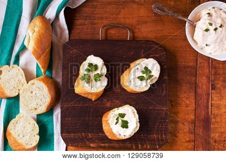 Delicious appetizer with freshly baked French bread and savory cream on a wooden table