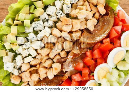 Traditional American Cobb Salad - Colorful entree  salad with bacon, chicken, eggs and tomatoes. Closeup as background