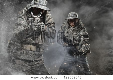 Two Special forces soldiers men holding a machine gun go ahead through the fog and the dust from the explosion on dark background