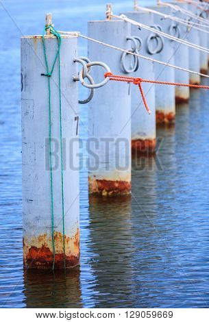 harbor quayside mooring metal bollards with rope in marina outdoor