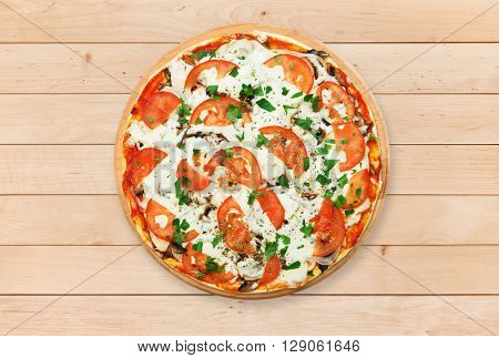 Delicious pizza with mushrooms, tomatoes and chicken meat - thin pastry crust at wooden round desk and wood background. Italian food. Top view
