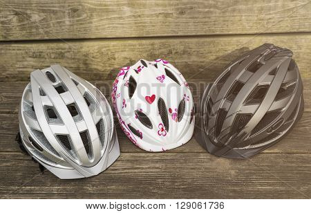 bicycle helmets of different sizes lying on a wooden bench, concept for family and security