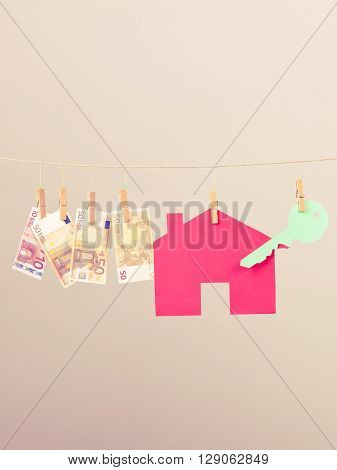 Red house with green key and banknotes cash hang on laundry line. Selling and buying home concept.