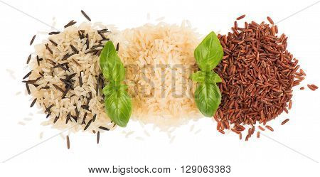 Top view of rice variety (black rice white rice red rice) decorated with green basil isolated on white background.