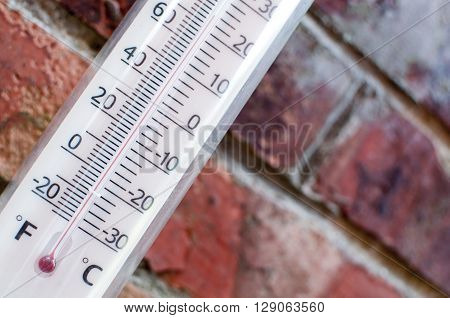 Thermometor measuring hot summer weather with a brick wall background