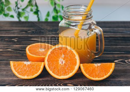 Orange, half of orange, orange lobule, jar of juice on the wooden table