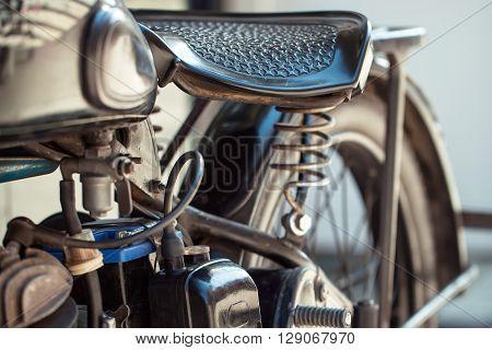 Old motorcycle vintage motor vehicle with steel frame saddle wheel on blurred background