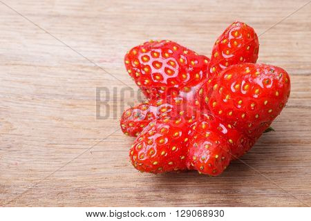 Healthy nutrition diet food modification. Red odd single strawberry fruit on wooden table board copy space text area