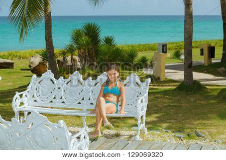 Smiling joyful, happy girl enjoying her leisure time by sitting on old style metal bench under the bright sunlight against azure crystal clear tranquil ocean background in tropical garden