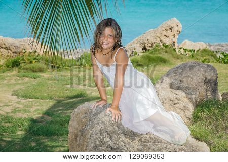 Little pretty, happy girl looking mermaid sitting on the rocks in tropical garden against tranquil clear ocean background
