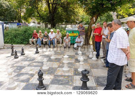 SARAJEVO BOSNIA AND HERZEGOVINA - SEPTEMBER 4 2009: Senior men preoccupied with an outdoor giant chess game