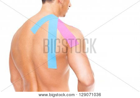 Muscular man with kinesiotaping on the shoulder, isolated on white background