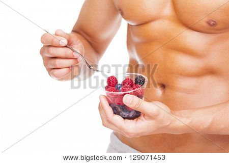 Fit man holding a bowl of fresh red fruits, isolated on white background