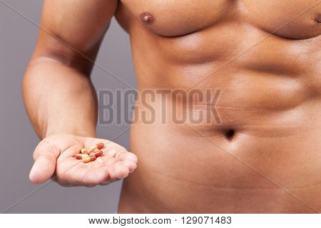 Muscular man with his hand full of pills on grey background