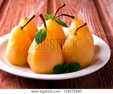 Poached pears with mint on white plate, wooden background