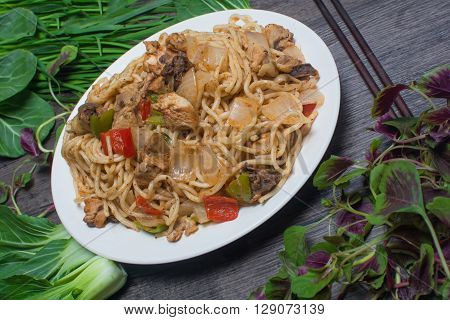 Chinese boiled noodles with a chicken and vegetables on the wooden background