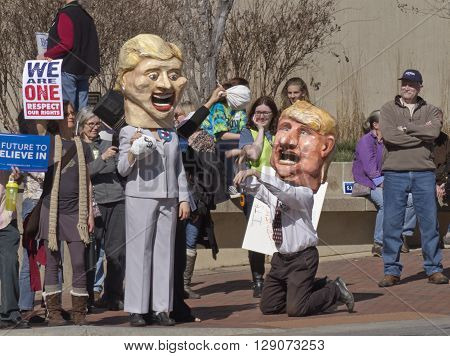 Asheville, North Carolina, USA - February 28, 2016: Humorous effigies of Donald Trump kneeling at Hillary Clinton's feet as she holds up a bag of money while skeptical Bernie Sanders supporters holding signs watch at a Bernie Sanders campaign rally
