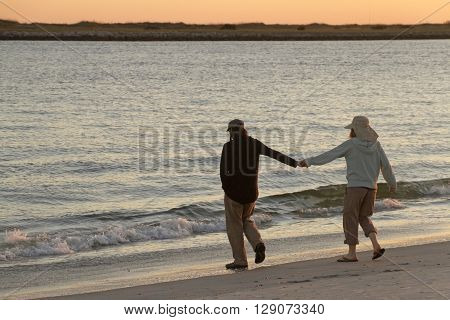 Wrightsville Beach, North Carolina, USA - November 13, 2015: A young couple hold hands on a scenic beach near dusk as he leads her towards the ocean's incoming tide at dusk