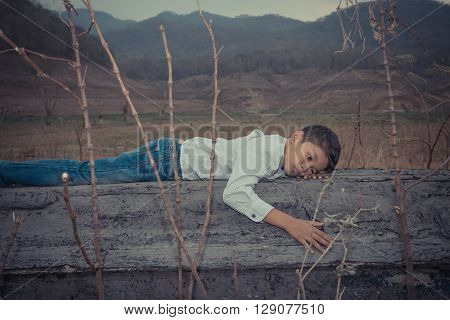 scared and alone, young homeless Asian child who is at high risk of being bullied and abused, selective focus
