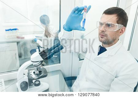 Skillful male scientist is doing experiment with samples. He is holding a flask and looking at it with seriousness. His female assistant is sitting and writing on background