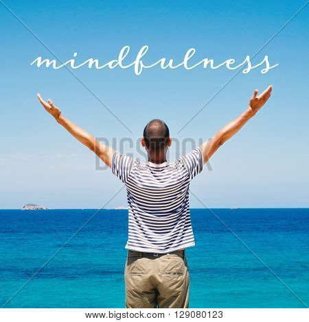 a young caucasian man seen from behind with his arms in the air saluting the new day in front of the sea and the text mindfulness