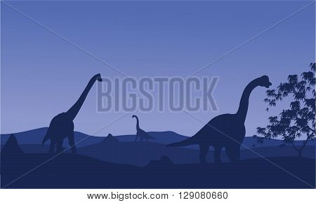 Silhouette of brachiosaurus with blue backgrounds in hills