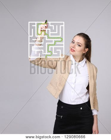 Young woman finding the maze solution, writing on whiteboard.