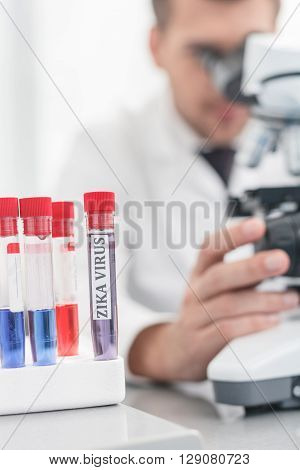 Cheerful young scientist is analyzing zika virus samples. Man is sitting and looking into the microscope. Focus on flasks on the table