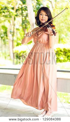Young woman playing violin in garden