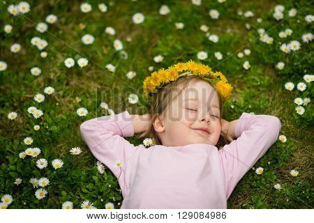 Little girl with dandelion wreath on head lying in grass full of daisy flowers - above view