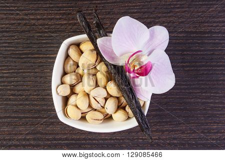 Pistachio nuts in white bowl colorful blooming orchid flower and fresh fragrant vanilla sticks pods on wooden background cosmetics ingredients