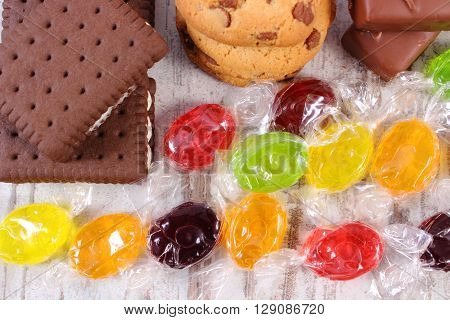 Heap of colorful candies and cookies on old wooden background too many sweets unhealthy food and reduction of eating sweets