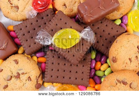 Heap of colorful candies and cookies on old wooden background too many sweets unhealthy food and reduction eating sweets