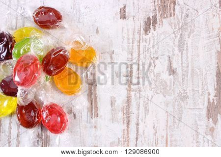 Frame of colorful candies with copy space for text on old wooden background too many sweets reduction of eating sweets