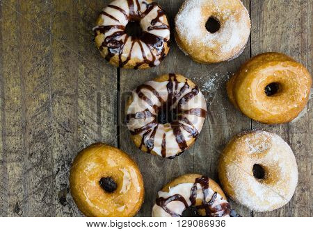 Top view photo of six doughnuts on rustic wood table