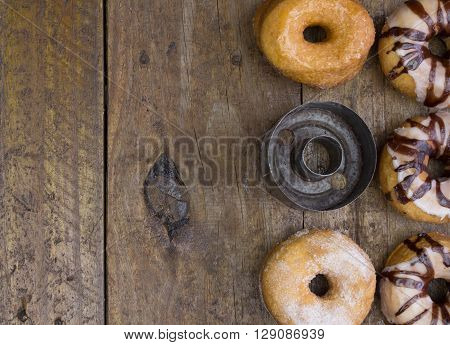 Top view photo of five doughnuts and a vintage cutter on rustic wood background