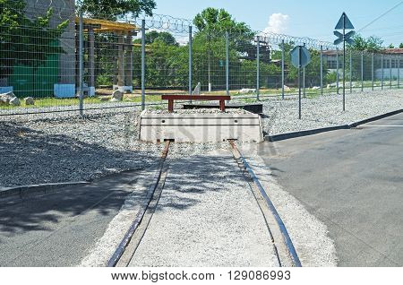 End of rail in an industrial area on against the background of a fence with barbed wire