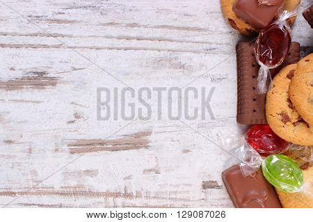 Colorful candies and cookies with copy space for text on old wooden background too many sweets concept of reduction eating sweets