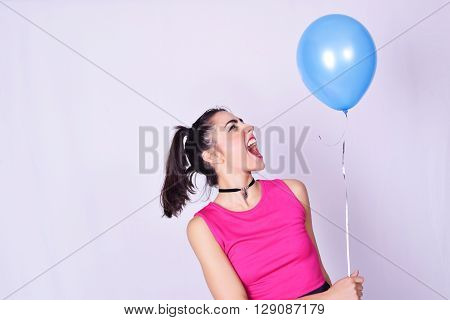 Portrait of fashionable young woman wearing stylish urban clothes while holding a balloon. Fashion studio portrait over grey backgroung.