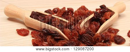 Heap of brown raisins with wooden spoon lying on wooden table healthy food and nutrition