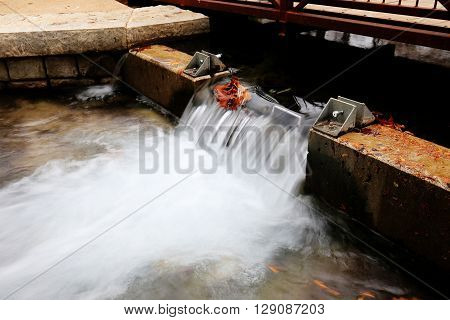 Smooth flowing water over dam with fall foliage