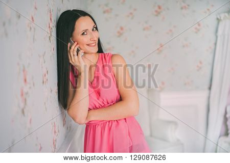 Young woman in red dress phone talking. Young Woman Busy with her Mobile Phone. Portrait of young woman phone call. Talking mobile phone woman.