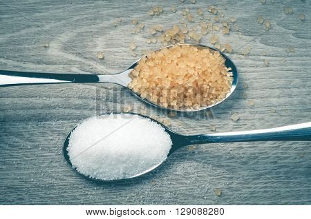 White sugar and brown sugar and a spoon on a wooden floor.