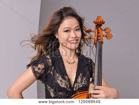 asian young girl with big violin-gray background