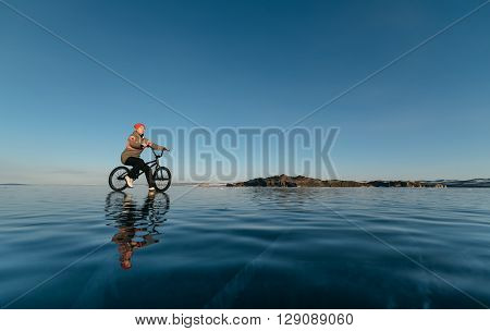 A girl sits on a bmx on the beautiful and dangerous ice.