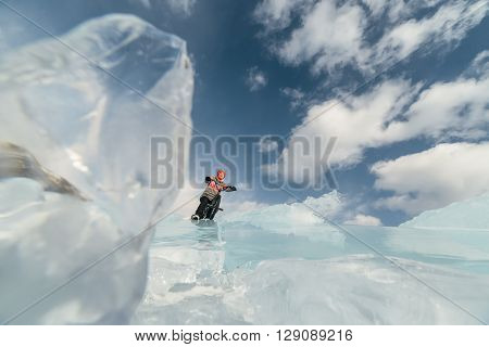 Girl standing on a bmx on the beautiful and dangerous ice. Ice the deepest lake in the world. This is Lake Baikal.